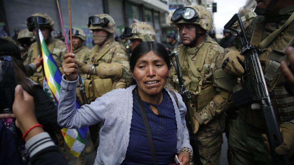 Foto: Indígenas y simpatizantes del expresidente Evo Morales bajo la vigilancia de policías, en La Paz (Bolivia). (EFE)