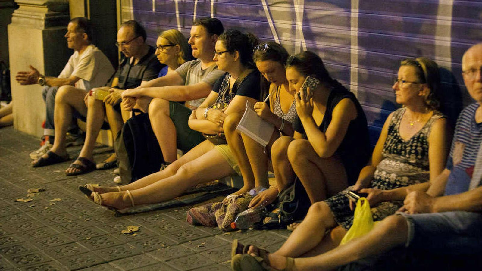 Foto:  Varios viandantes esperan en una zona acordonada de las Ramblas. (Reuters)