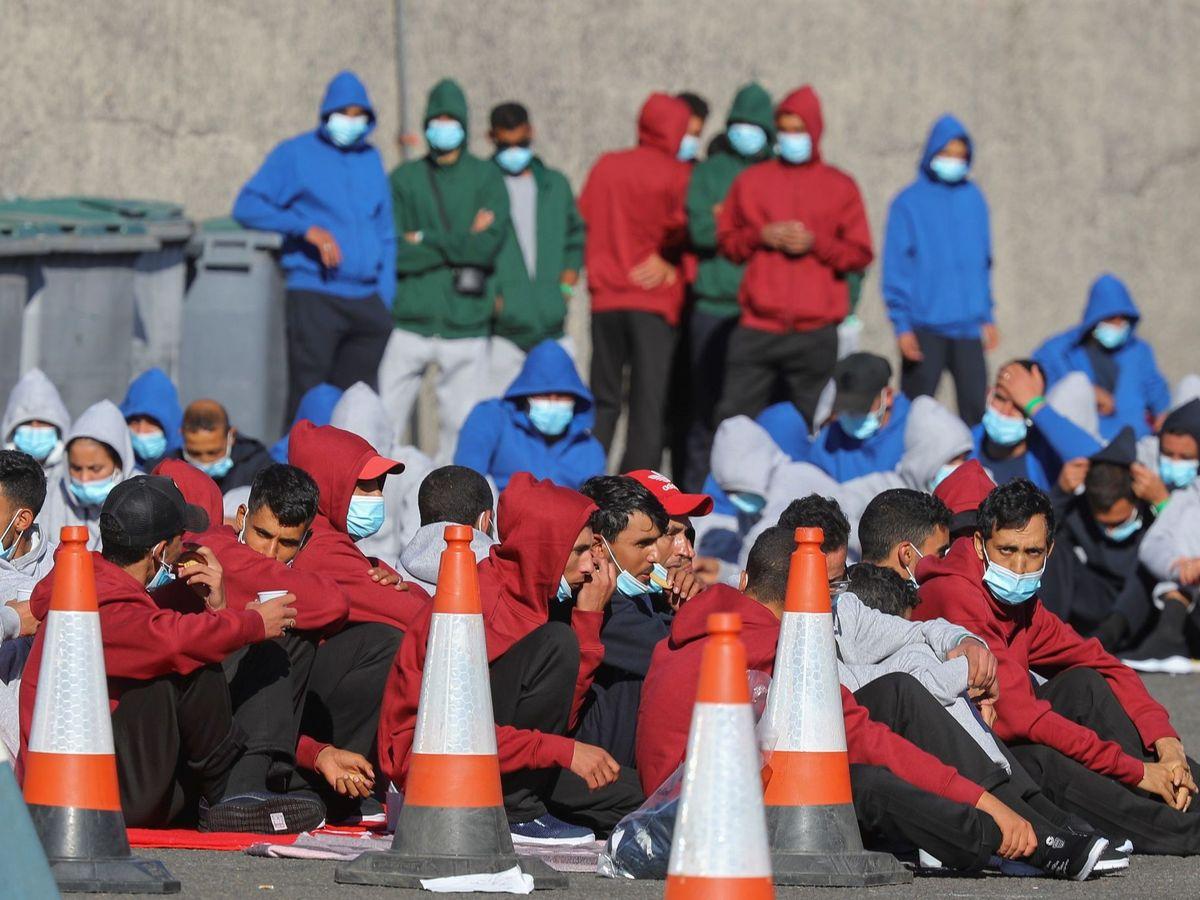 Foto: Un grupo de migrantes en el muelle de Arguineguín. (EFE)