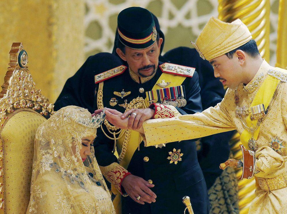 Foto: El sultán de Brunei, Hassanal Bolkiah, sostiene la mano de su hijo para bendecir a su nueva esposa durante la ceremonia en el palacio Nurul Iman. (Reuters)