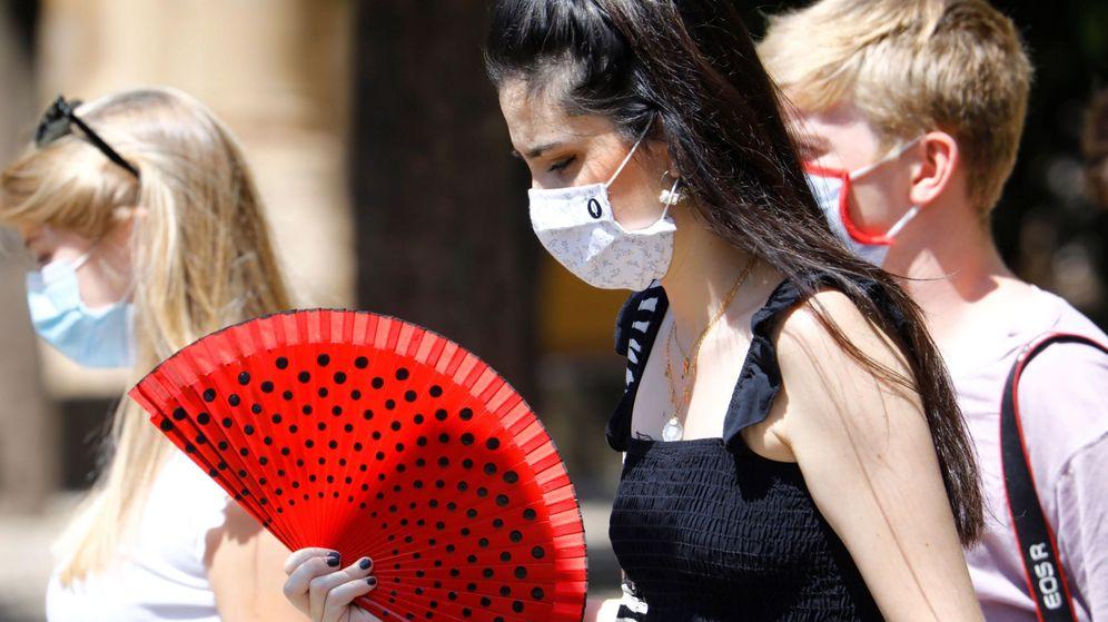 Foto: Varias mujeres pasean con mascarilla y abanico por una calle de Córdoba (EFE)