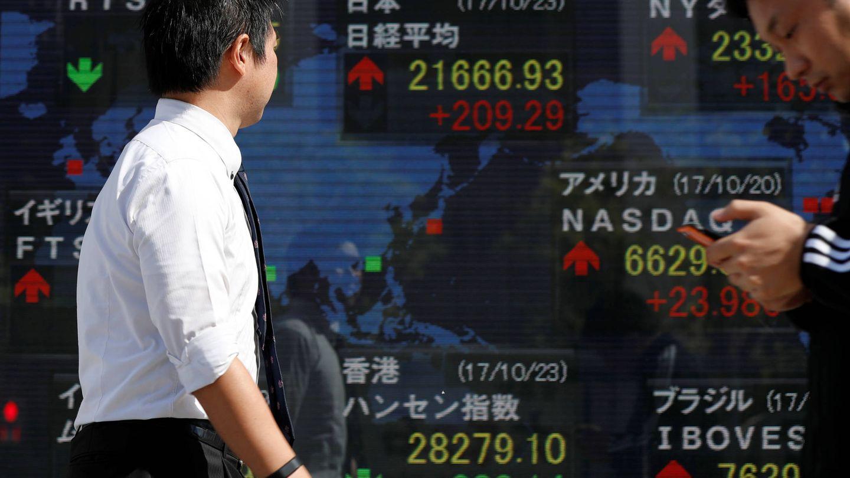 Japoneses pasan ante una pantalla con las cotizaciones de bolsa, en Tokio. (Reuters)