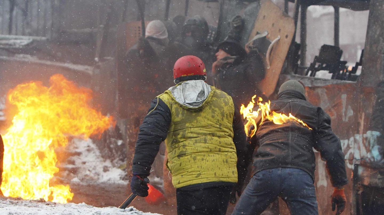 Manifestantes se protegen tras un autobús quemado en Kiev (Reuters).