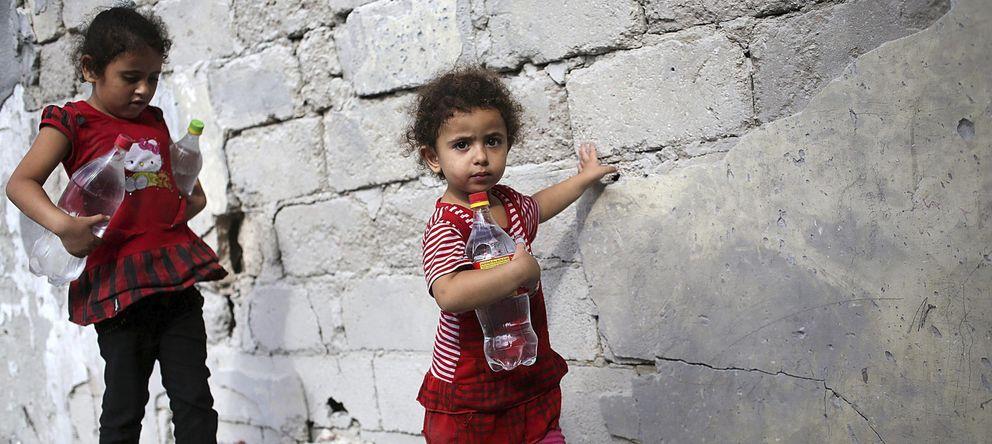 Foto: Dos hermanas palestinas llevan botellas de agua potable a su casa. (EFE)