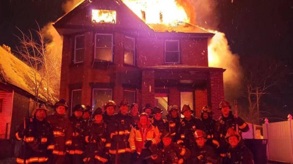 Foto: Los 18 miembros del cuerpo de bomberos de Detroit, posando sonrientes mientras la casa arde a su espalda (Foto: Twitter)