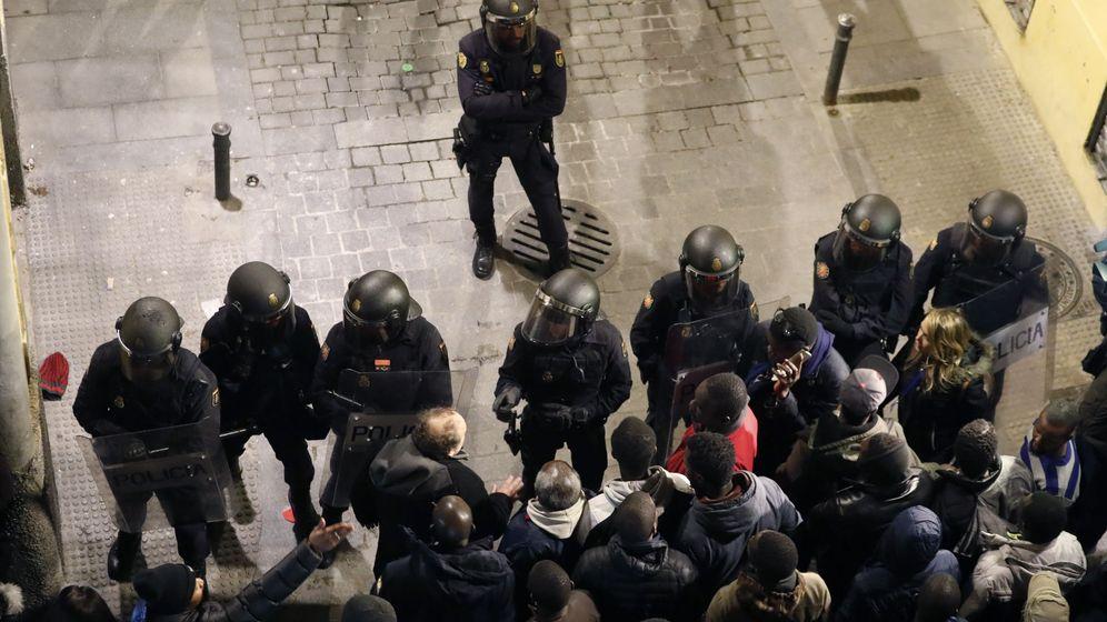 Foto: Policías antidisturbios intentan calmar la tensión en el barrio de Lavapiés. (EFE)