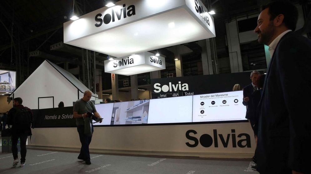 Foto: Unos visitantes pasan ante el expositor de Solvia, en el salón inmobiliario Barcelona Meeting Point. (Efe)