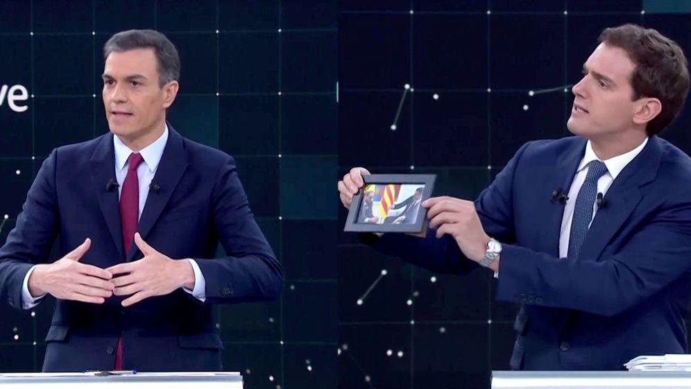 Foto: Albert Rivera saca una foto de Pedro Sánchez y Quim Torra durante el debate. (Reuters)