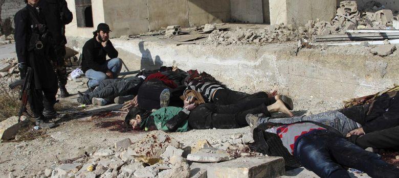 Foto: Combatientes rebeldes antes los cuerpos de yihadistas del ISIS ejecutados en Alepo (Reuters).