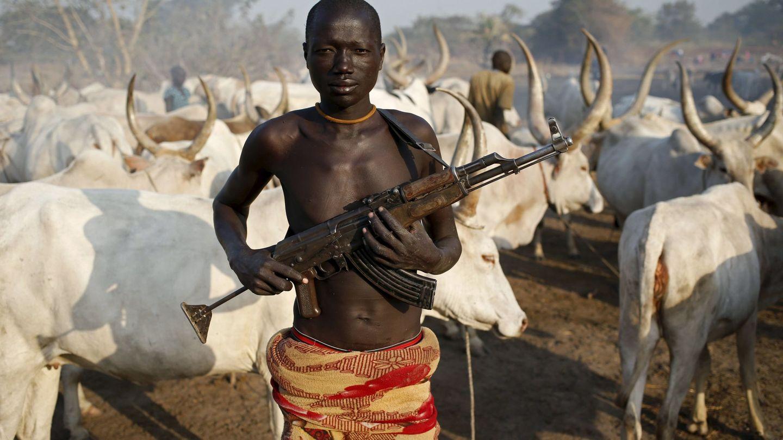 Un miembro de la tribu dinka sostiene su rifle AK47 ante un rebaño de vacas cerca de Rumbek, Sudán del Sur. (Reuters)