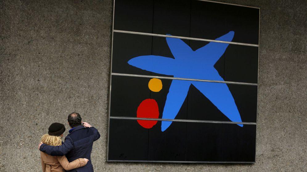 Foto: Una pareja saca una fotografía frente a un cartel de Caixabank. (Reuters)