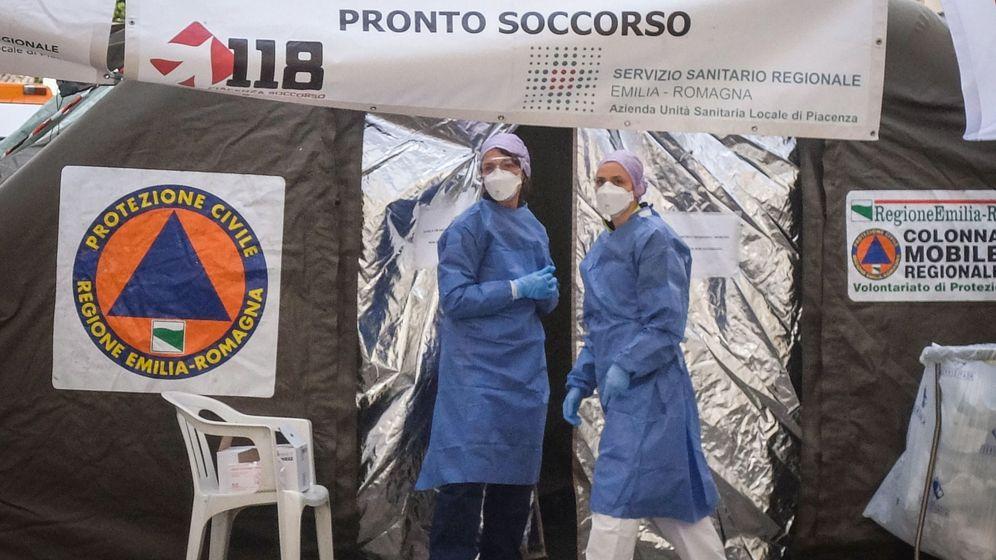 Foto: Dos sanitarios usan trajes protectores y máscaras de atención médica frente a la unidad médica avanzada construida fuera de la sala de emergencias del hospital Piacenza. (EFE)
