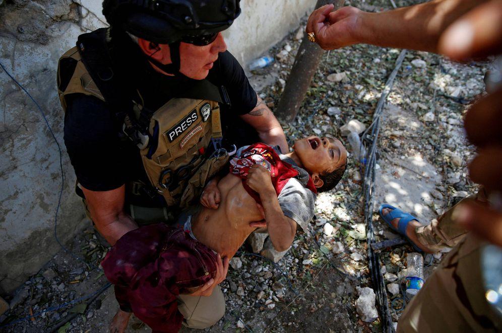 Foto: Un soldado da agua a un niño deshidratado rescatado por el Ejército iraquí en el frente de Mosul. (Reuters)