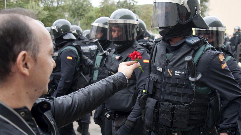Foto: Un hombre ofrece un clavel a un agente de la Guardia Civil en el centro de votación de Sant Julià de Ramis (Girona). (EFE)