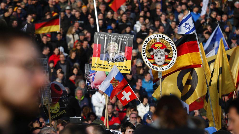 Foto: Seguidores de PEGIDA sostienen carteles contra Angela Merkel durante una manifestación en Dresde. (Reuters)