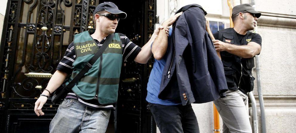 Foto: Dos agentes de la Guardia Civil escoltan a un detenido durante la Operación Púnica. (EFE)