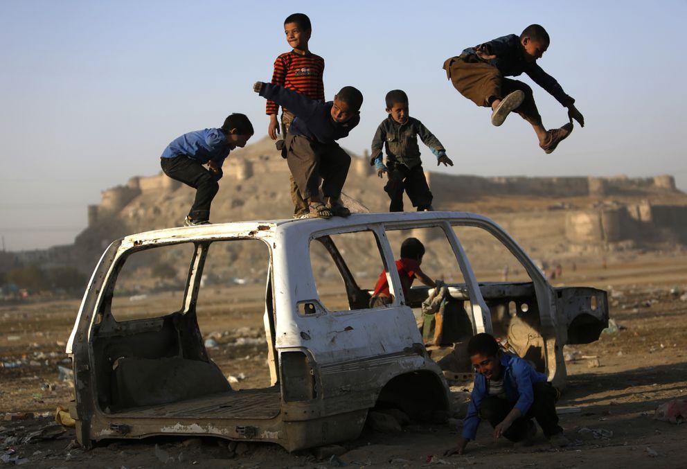 Unos niños afganos juegan con los restos de un coche en las afueras de Kabul. (Reuters)