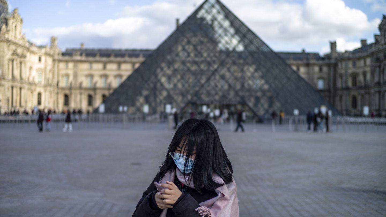 Una persona con mascarilla frente al Museo del Louvre, en París. (Reuters)