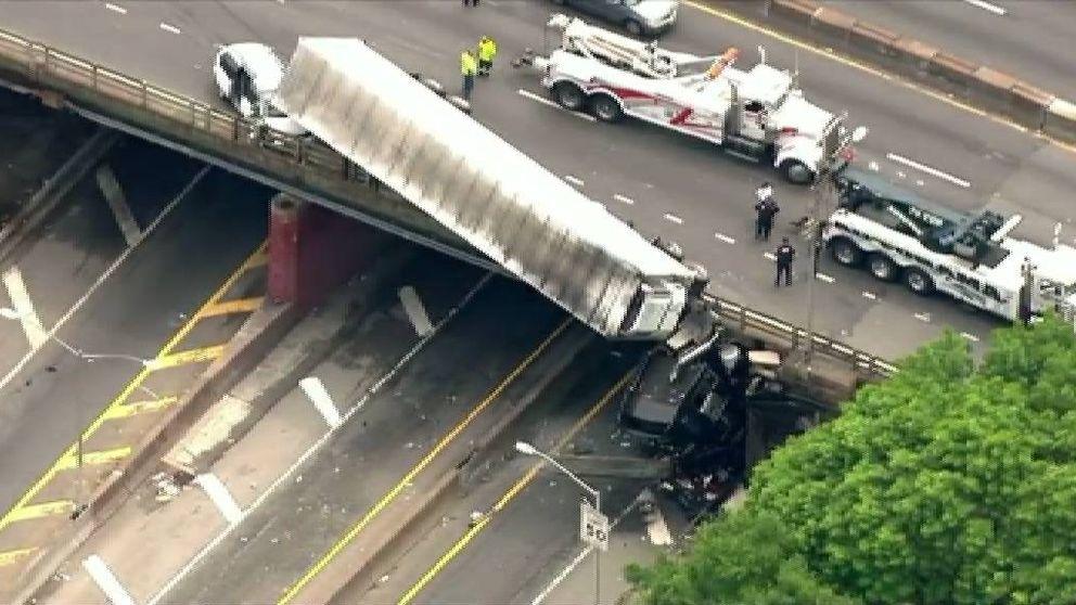 Aparatoso accidente en una autopista de Nueva York: se queda colgando de un puente el tráiler de un camión