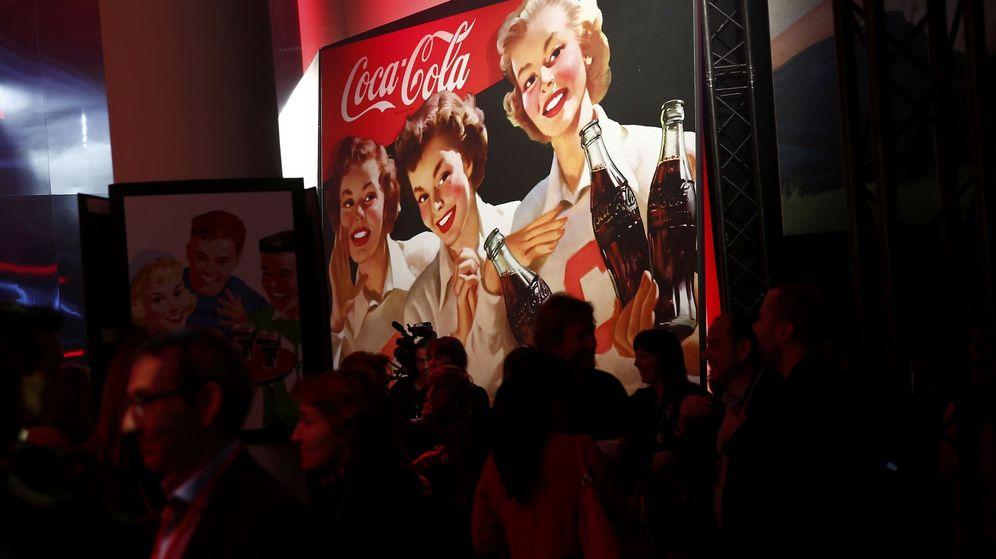 Foto: Presentación de Coca-Cola con el logo al fondo.
