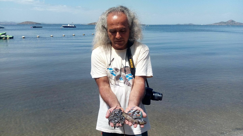 Pedro García, director de ANSE, mostrando peces recogidos en la orilla del Mar Menor. (EFE)