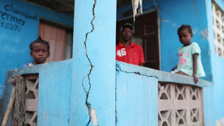 Foto: Un hombre y dos niños en el porche de su casa, dañada por un terremoto en Port-de-Paix, al norte de Haití, el pasado 8 de octubre de 2018. (Reuters)