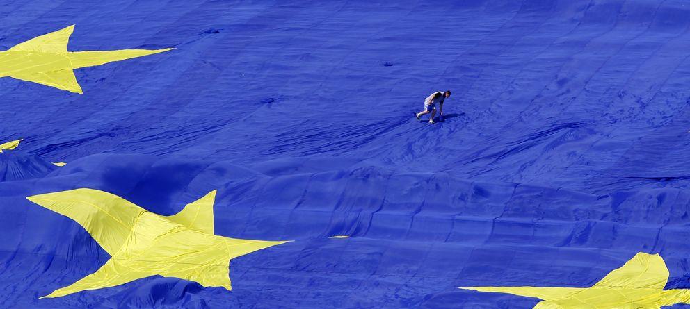 Foto: Un trabajador colabora en el despliegue de una inmensa bandera de la Unión Europea en el Día de la UE, en Bucarest (Reuters).
