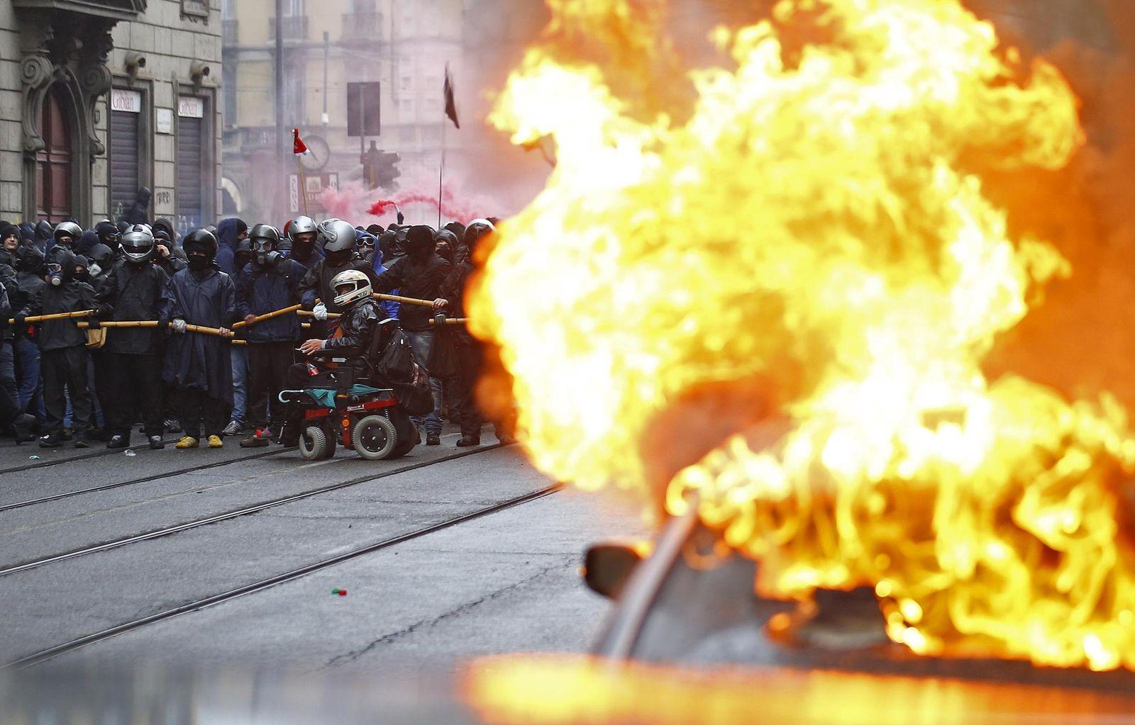 Foto: Un coche arde ante un ingente cordón policial en Milán (Reuters).