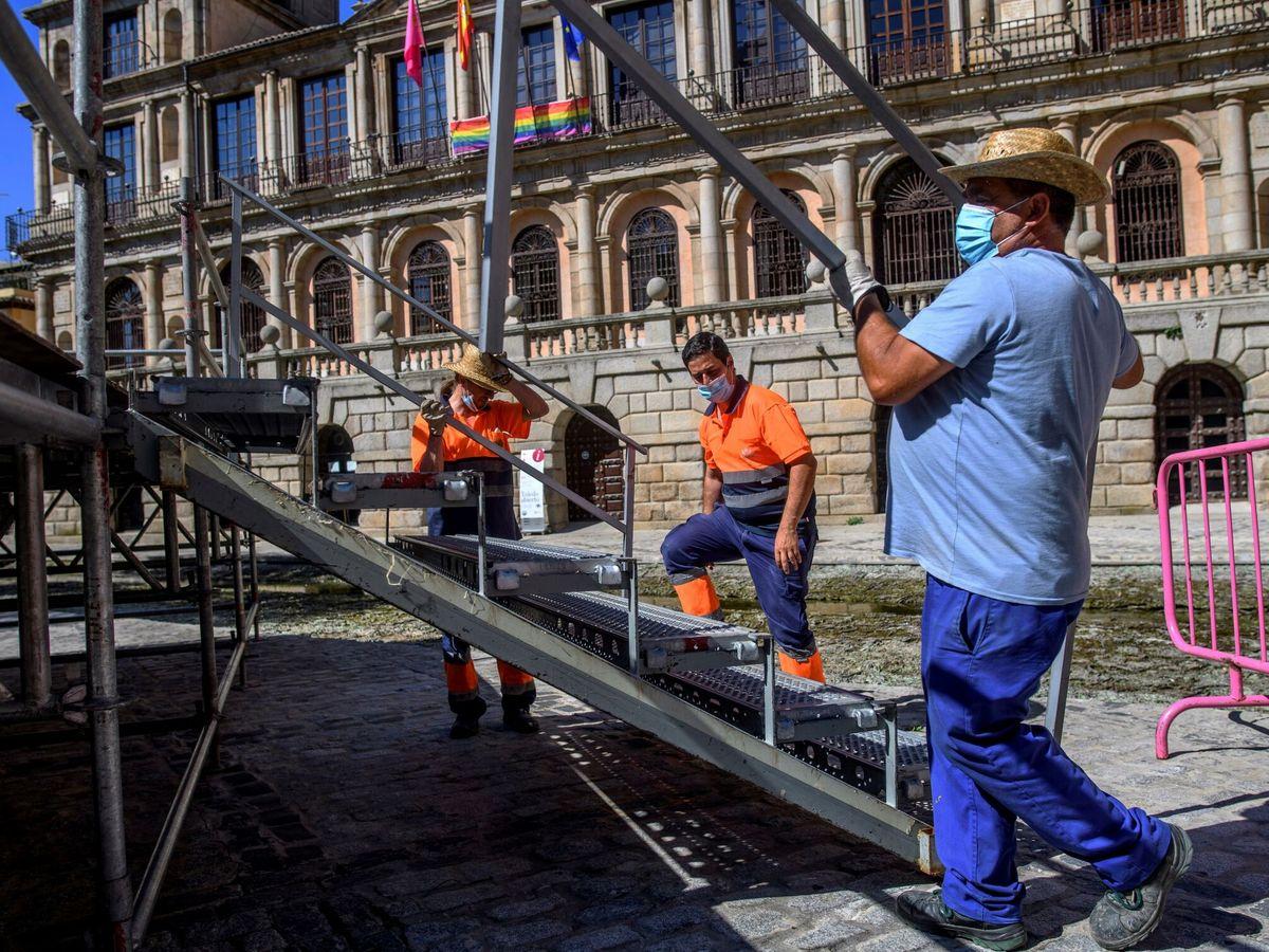 Foto: Varios operarios trabajan en el centro de Toledo. (EFE)
