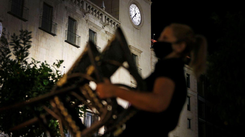 Una trabajadora de la hostelería recoge una terraza en Alicante antes del toque de queda (EFE)