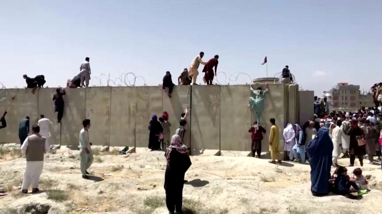 Foto: Unas personas escalan un muro de alambre de espino para entrar en el aeropuerto de Kabul, Afganistán. (Reuters)