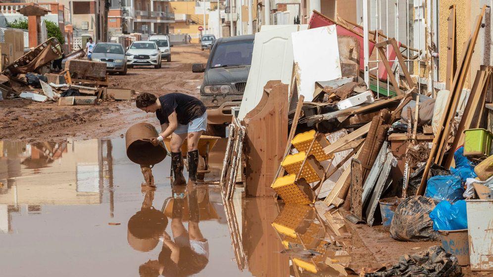 Foto: Una mujer vierte lodo en la calle en la localidad de Los Nietos. (EFE)