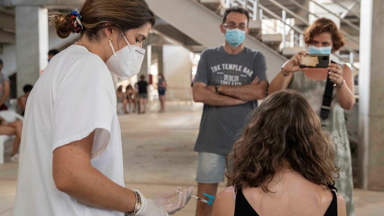 Una enfermera administra la vacuna de Moderna a una joven en el estadio Enrique Roca, de Murcia. (EFE)