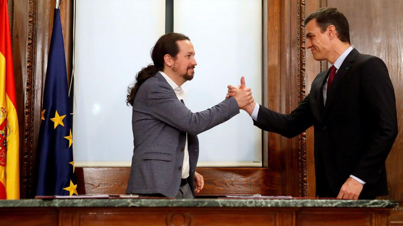 Pedro Sánchez y Pablo Iglesias estrechan sus manos tras rubricar su acuerdo programático de coalición, este 30 de diciembre en el Congreso. (EFE)