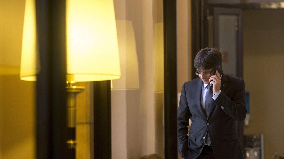 Foto: El presidente de la Generalitat, Carles Puigdemont, habla por teléfono en los pasillos del Parlamento de Cataluña. (EFE)