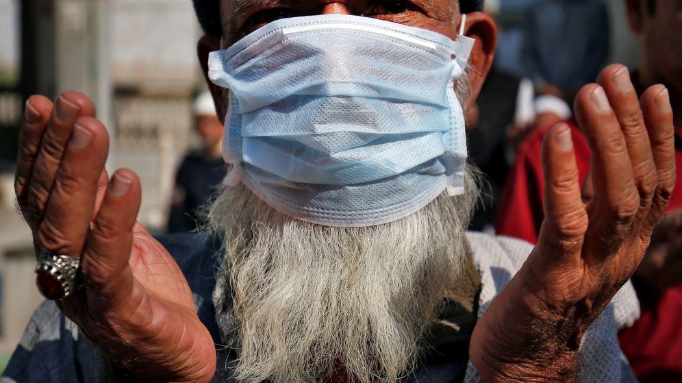 Foto: Un musulmán con mascarilla reza por las víctimas del coronavirus en una mezquita en Ahmedabad, India. (Reuters)