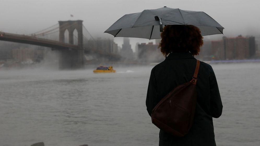Foto: Una mujer con un paraguas frente al Puente de Brooklyn, el pasado 12 de enero de 2018. (Reuters)