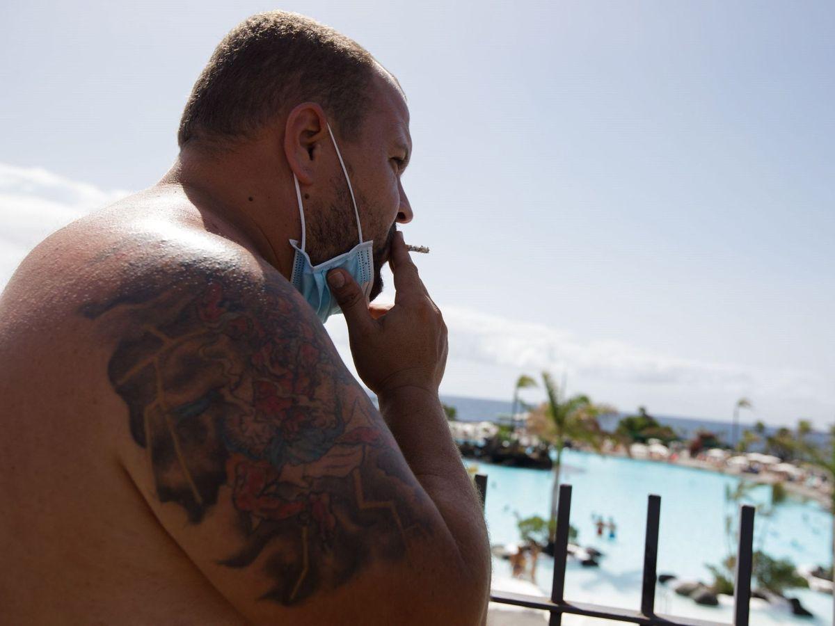 Foto: Un hombre se baja la mascarilla para fumar. (EFE)