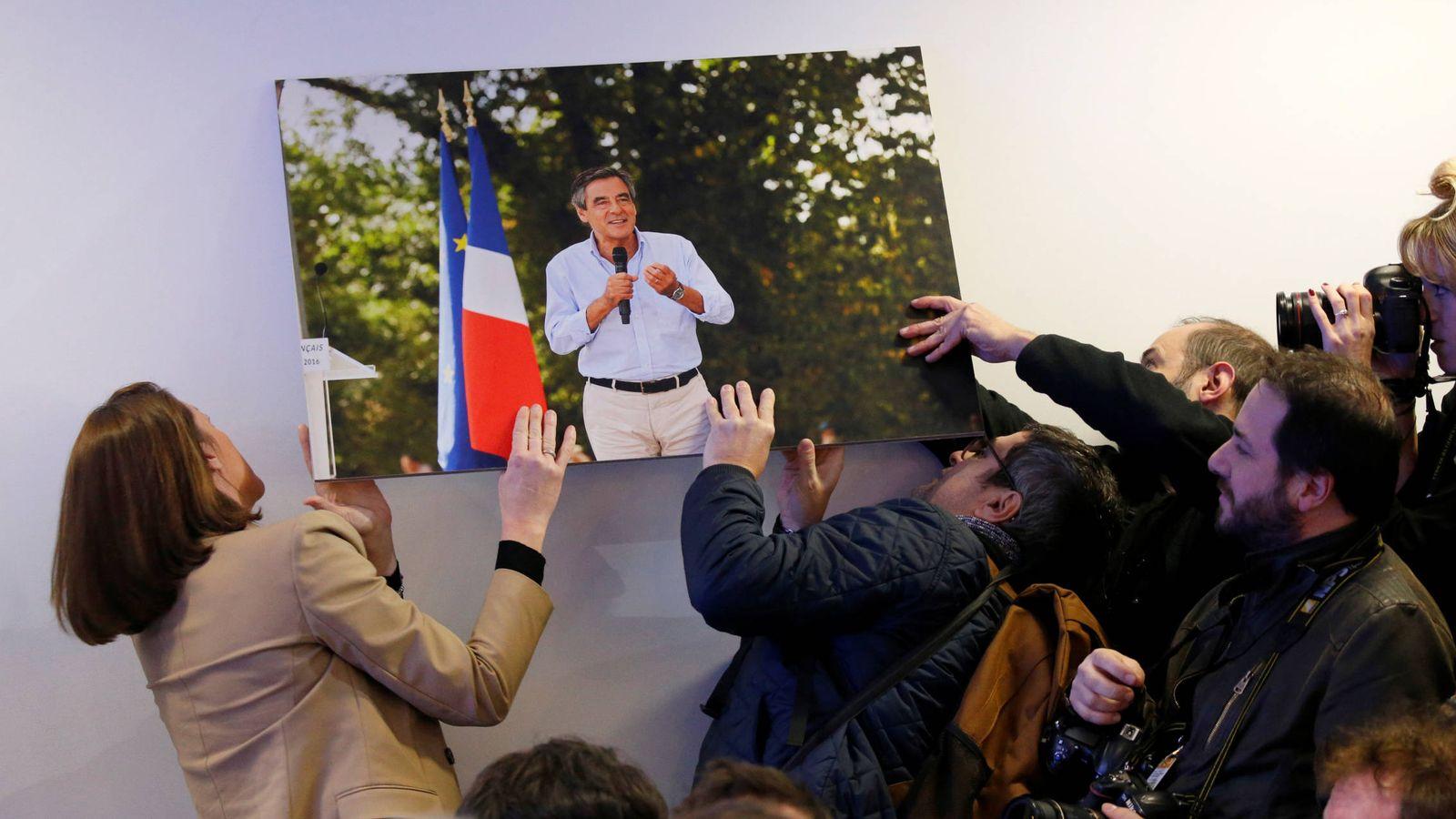 Foto: Periodistas intentan colgar una fotografía de François Fillon que se había caído antes de su rueda de prensa en París. (Reuters)