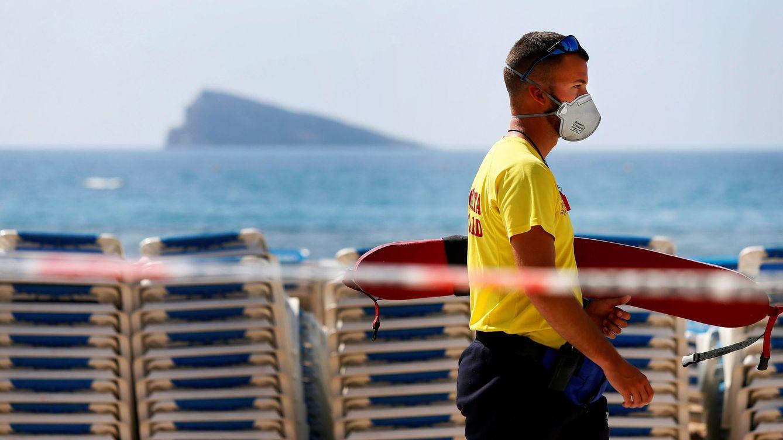 Foto: n socorrista camina con máscara por la playa de levante de Benidorm (Alicante). (EFE)