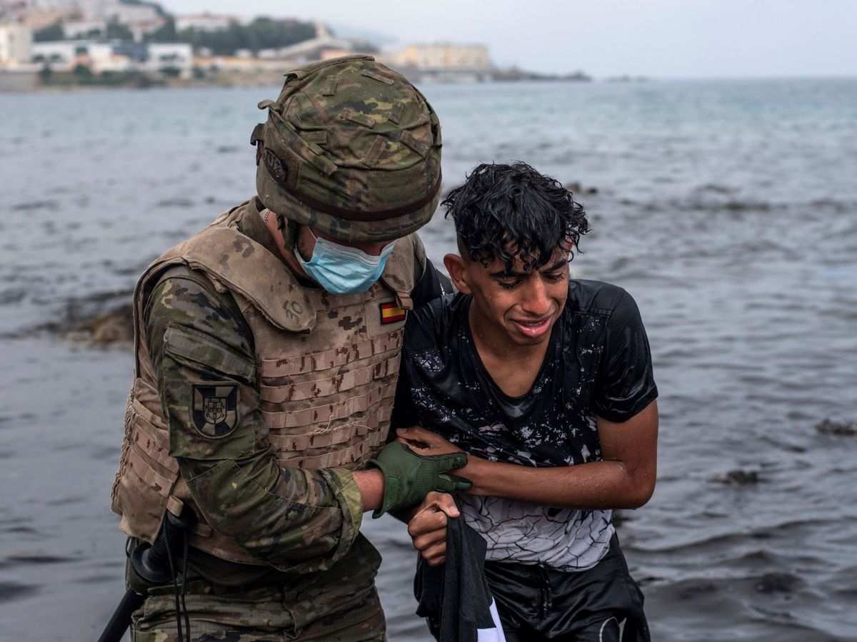 Foto: Un soldado ayuda a un inmigrante a salir del agua. (EFE)