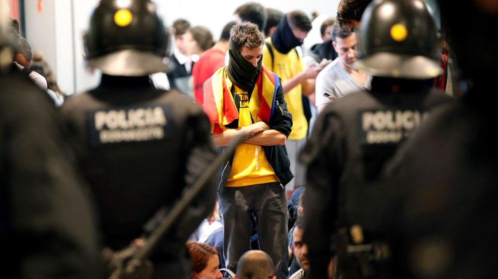 Foto: Activistas independentistas, frente a los Mossos en El Prat. (EFE)