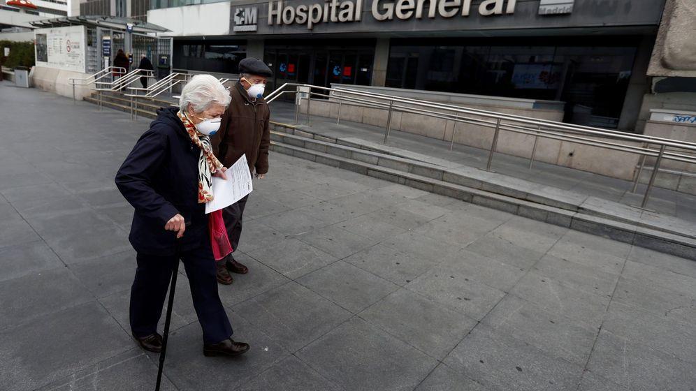 Foto: Una pareja de ancianos pasa ante el Hospital de La Paz, en Madrid. (EFE)