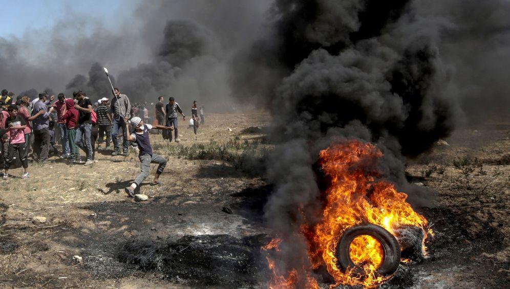 Foto: Manifestantes lanzan piedras contra soldados israelíes durante unas protestas en la frontera de Gaza e Israel, el 14 de mayo de 2018. (EFE)