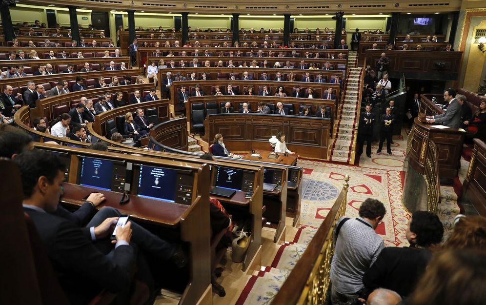 Foto: Pedro Sánchez consulta su móvil mientras Antonio Hernando sigue su intervención durante el debate de investidura, este 27 de octubre. (EFE)