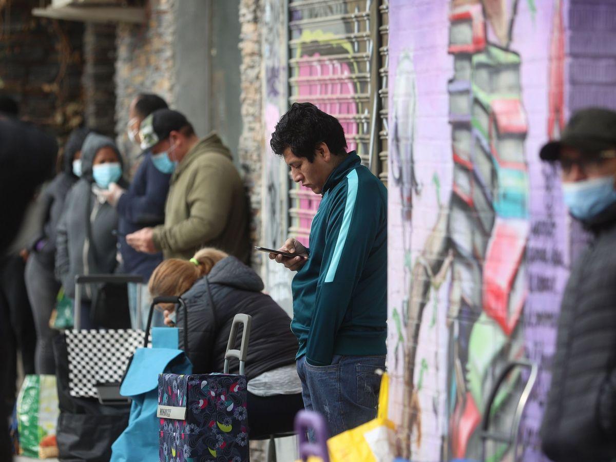 Foto: Un hombre mira el móvil mientras espera para recoger alimentos en Aluche, Madrid (EFE)