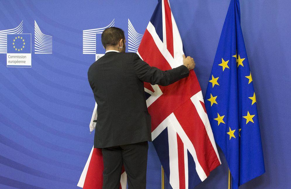Foto: Un empleado de la Comisión Europea coloca una bandera británica junto a otra de la UE antes de la reunión de Cameron y Juncker en Bruselas (Reuters).
