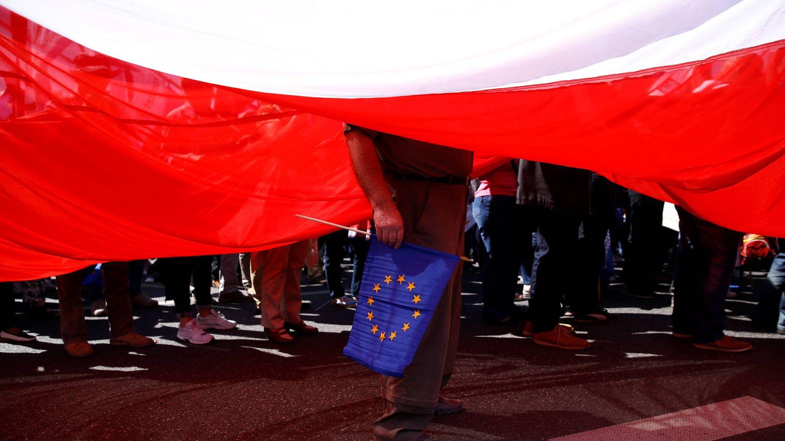 Foto: Un hombre sostiene una bandera de la UE junto a una enorme bandera polaca durante una protesta en Varsovia (Reuters).