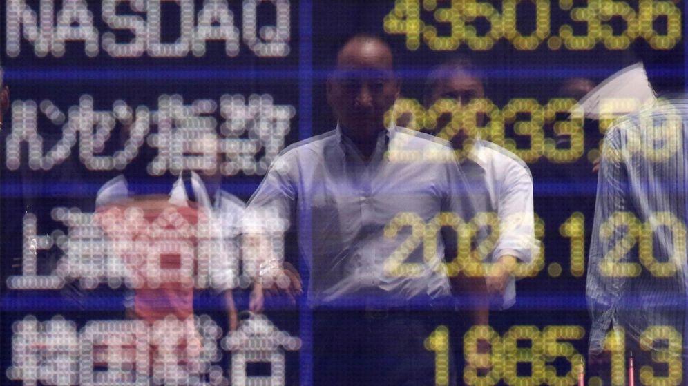 Foto: Reflejo de un hombre frente a un panel con varios índices. (Reuters)