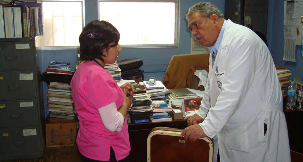 El doctor Gotuzzo habla con una trabajadora en su despacho.